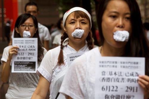 "Local artists bite photo copies of the white paper ""One country, two systems"" to simbolize people's speech has been disregarded and to urge people to vote in an unofficial referendum in Hong Kong"