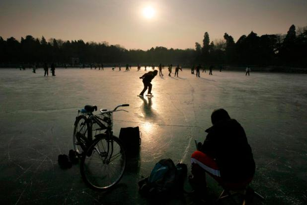 People skate on the frozen Wei Ming lake at Peking University in Beijing January 4, 2008. The lake is a popular spot during the winter months for skating, but has only in the last week frozen enough to allow people to do so.        REUTERS/David Gray      (CHINA) - RTX57GZ